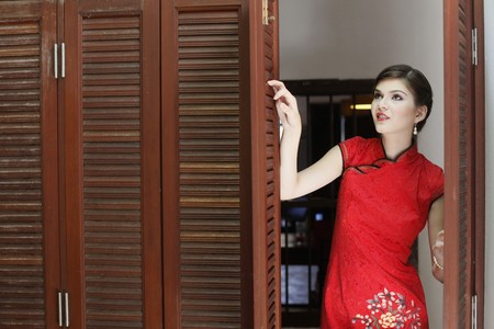 Woman in cheongsam looking through open window Stock Photo - 7131740