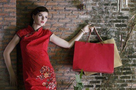 Woman in cheongsam carrying shopping bags Stock Photo - 7131767