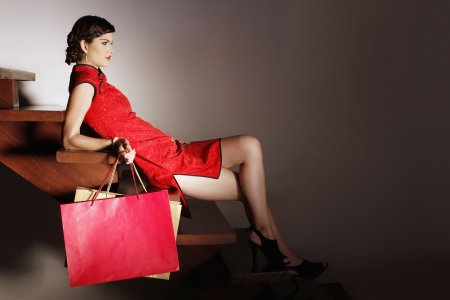 Woman sitting on stairs carrying shopping bags