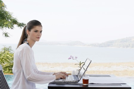 Woman contemplating while using laptop photo