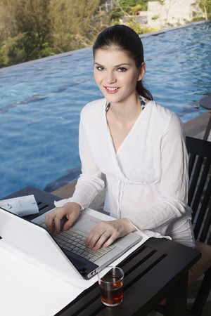 Woman using laptop by the pool side Stock Photo - 7131723