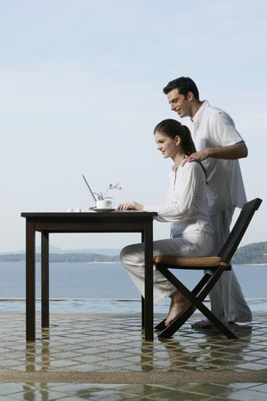 Woman using laptop by the pool side, man watching from behind Stock Photo - 7131734