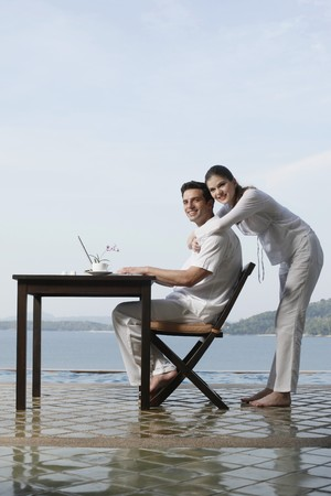 Man using laptop, woman hugging him from behind  photo