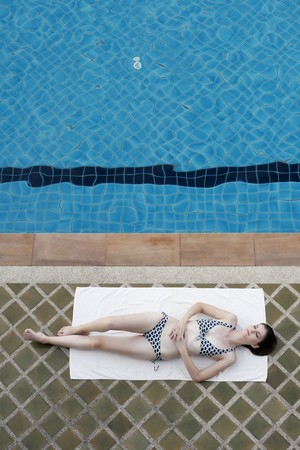 Woman sunbathing beside a swimming pool photo