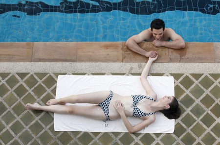 Man in swimming pool flirting with woman Stock Photo - 7131756
