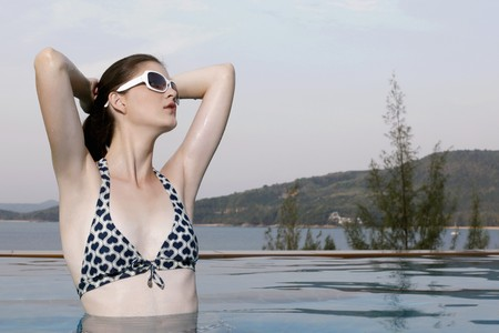 Woman with sunglasses posing in a swimming pool photo