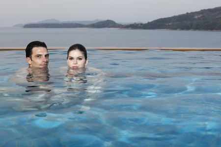 Man and woman in pool, heads half submerged in water photo