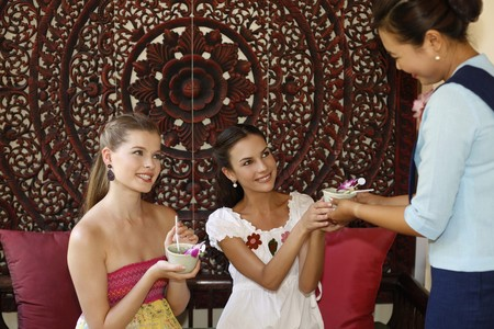 Customer service representative serving tea to women photo