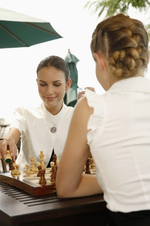 Businesswomen playing chess by the poolside Stock Photo - 7172754