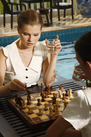 Businesswomen playing chess by the poolside Stock Photo - 7131693