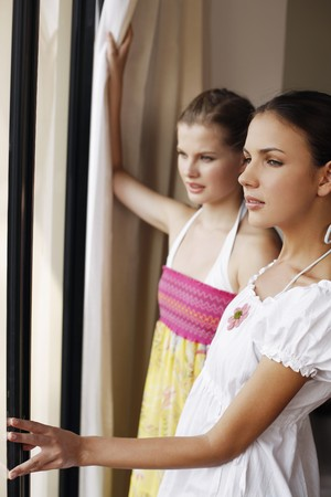 Women looking out of bedroom window Stock Photo - 7172781