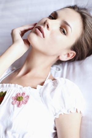 ukrainian ethnicity: Woman lying on bed, touching her face Stock Photo