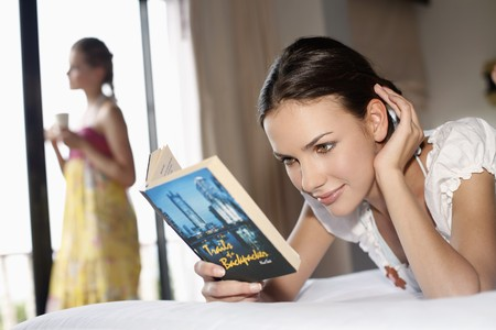 Woman reading book on bed, her friend holding a cup in the background Stock Photo - 7131648