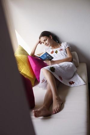 ukrainian ethnicity: Woman reading book on sofa Stock Photo
