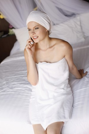 towel wrapped: Woman with towel wrapped around head talking on the phone