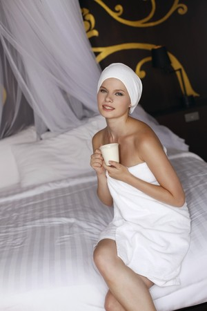 Woman wrapped in towel holding a cup of coffee photo