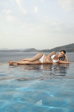 Woman lying on side at the edge of pool photo