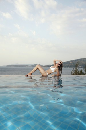 Woman sitting at the edge of pool Stock Photo - 7172772