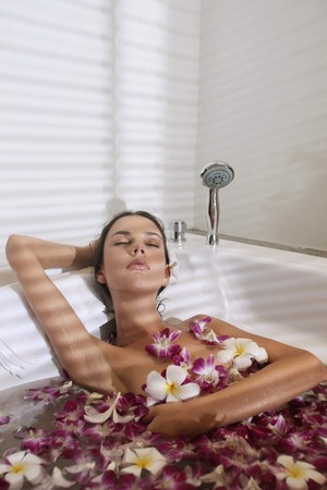 ukrainian ethnicity: Woman relaxing in bathtub with flower petals Stock Photo
