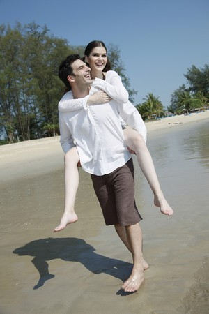 piggyback ride: Man giving woman a piggy back ride on beach