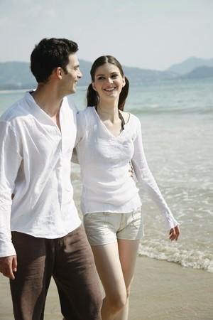 parejas caminando: Hombre y mujer caminando a lo largo de la playa  Foto de archivo
