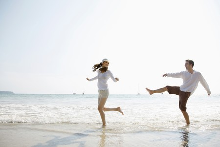 southeastern european descent: Man and woman playing on beach