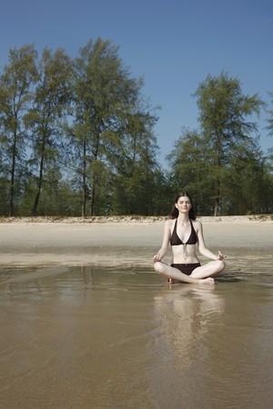 southeastern european descent: Woman meditating on beach Stock Photo