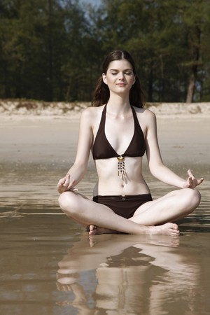 Woman meditating on beach Stock Photo - 7355976