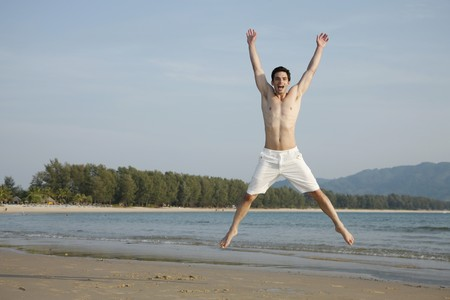 jacks: Man jumping jacks on beach Stock Photo