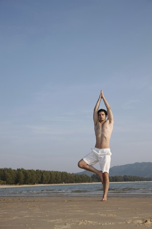 Man performing yoga on beach photo