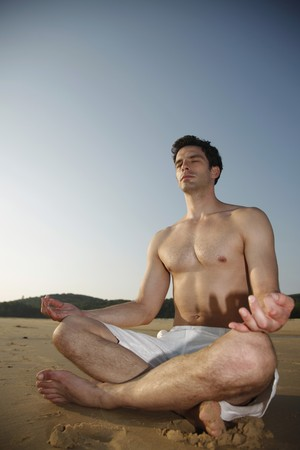 Man meditating on beach photo