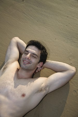 Man with bare chest lying down with eyes closed and hands behind head on beach photo