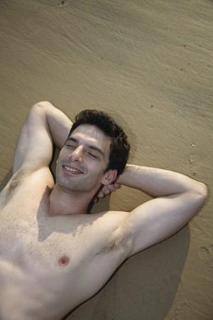 nackte brust: Mann mit nackten Brust liegend mit geschlossenen Augen und H�nden hinter dem Kopf am Strand  Lizenzfreie Bilder