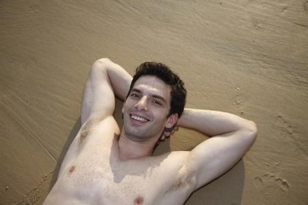 nackte brust: Mann mit nackten Brust, die mit den H�nden hinter dem Kopf am Strand liegend  Lizenzfreie Bilder
