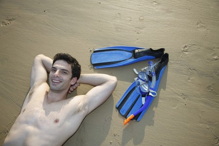 Man with bare chest lying down with hands behind head on beach Stock Photo - 7356210
