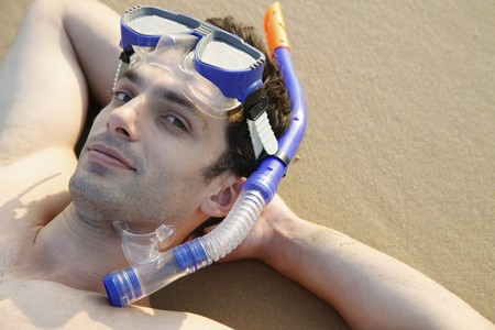 Man with scuba mask lying down with hands behind head on beach photo