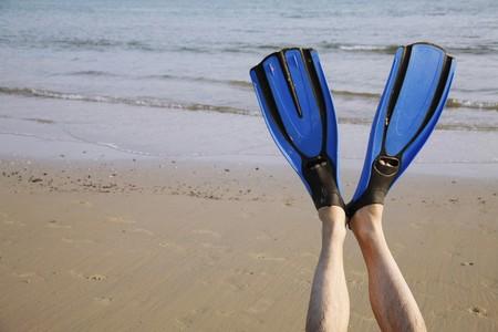 southeastern european descent: Legs wearing blue flippers Stock Photo