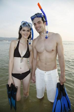 ni�o sin camisa: Hombre y mujer caminando en la playa con equipo de buceo superficial