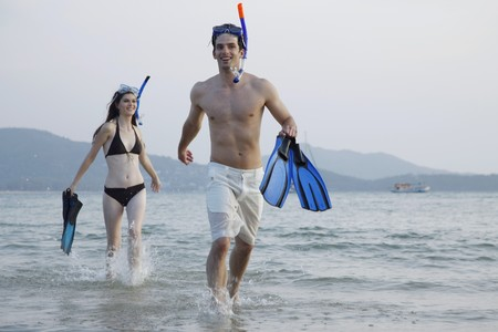 Man and woman running on beach with snorkeling gear photo