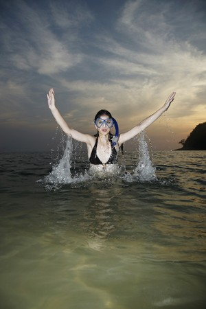 Woman with scuba mask emerging from sea photo