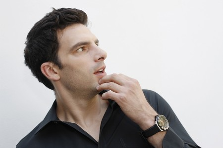 southeastern european descent: Man touching chin while looking to the side Stock Photo