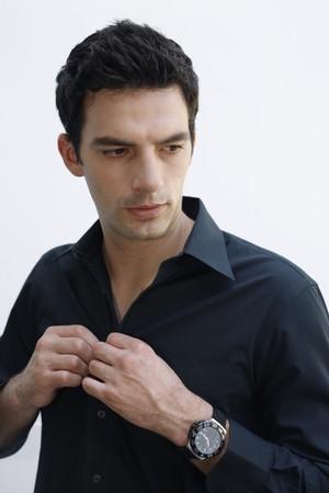 Man buttoning his shirt photo