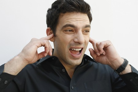 Man blocking his ears with fingers photo