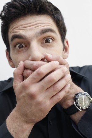 Man covering mouth with hands photo