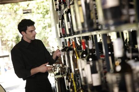 side bar: Man selecting wine bottle from rack