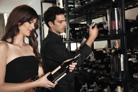 Man and woman selecting wine bottles from rack photo