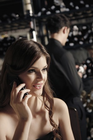 Woman talking on the phone, man selecting wine bottle in the background photo