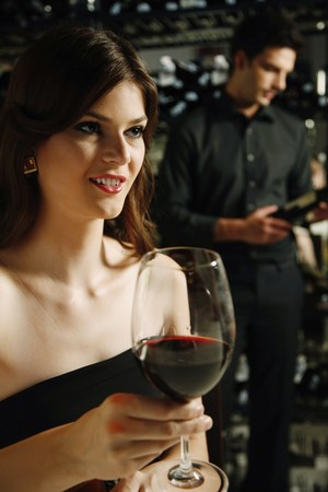 Woman with a glass of red wine, man selecting wine bottle in the background photo