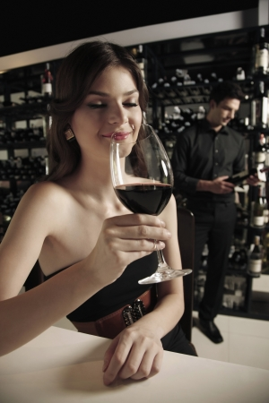 Woman with a glass of red wine, man selecting wine bottle in the background Stock Photo - 7360479