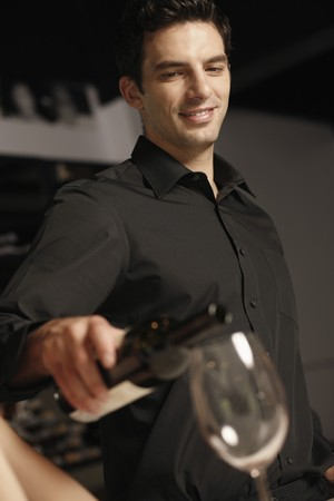 Man pouring wine into womans glass photo
